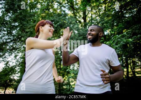 Giovani, gioiosi amici multietnici, uomo africano e donna caucasica, jogging e esercizio in natura, parco o foresta, guardandosi a vicenda e. Foto Stock