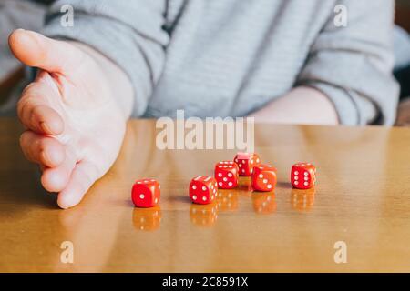 Mano femminile che lancia sei morse rosse sul tavolo. Yamb, gioco dei dadi Foto Stock