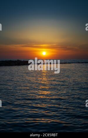 Tramonto meraviglioso sul mare all'orizzonte. La fine della giornata al mare. Colori della natura luminosi e intensi. Foto Stock