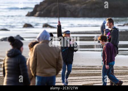 Bandon by the Sea, Oregon / USA - Febbraio 21 2020: Donna che cammina un labirinto di sabbia con una macchina fotografica d'azione e un piccolo cane nel suo mantello.