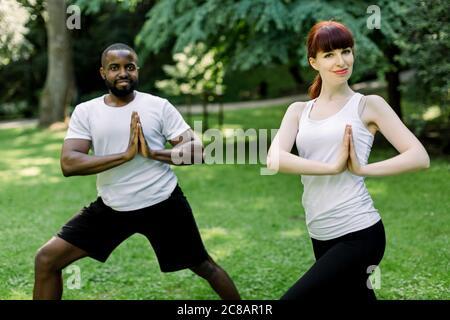 Giovane coppia multietnica, uomo africano e donna caucasica, facendo yoga in natura all'aperto, in piedi insieme con le mani in posizione di preghiera. Sano