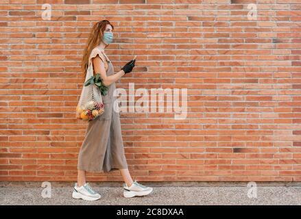 Giovane donna che indossa la maschera con lo smartphone mentre si cammina sentiero da muro di mattoni Foto Stock