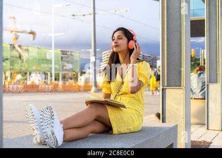 Giovane donna che ascolta la musica mentre si siede su una panca in cemento città Foto Stock