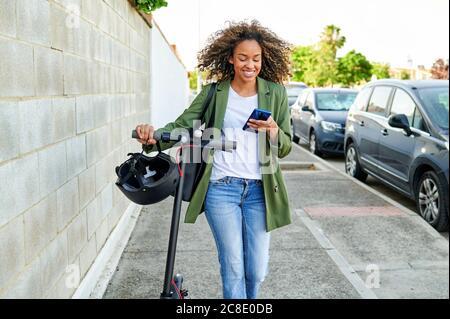 Felice giovane donna che usa lo smartphone mentre cammina con l'elettricità spingere lo scooter sul marciapiede