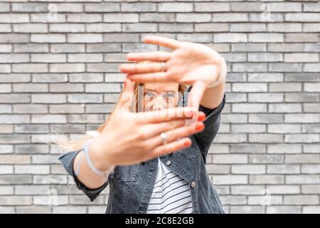 Primo piano di donna mid adult che fa cornice dito contro grigio muro di mattoni