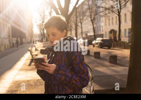 Ritratto di donna con zaino e caffè da andare guardando cellulare in serata, Berlino, Germania Foto Stock