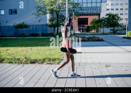 Giovane donna che tiene lo skateboard utilizzando lo smartphone mentre si cammina sentiero in città Foto Stock