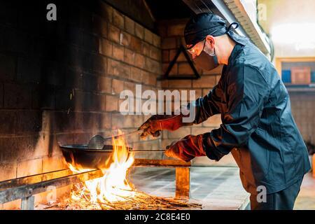 Cucina tradizionale di paella in cucina ristorante, chef con maschera protettiva