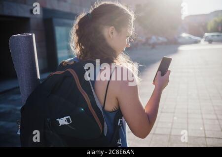 Giovane donna sportiva che usa lo smartphone mentre si cammina in città strada durante il giorno di sole