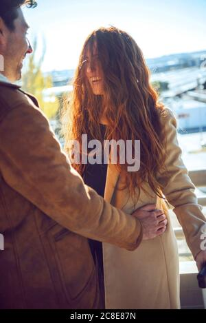 Allegra lunga donna dai capelli rossi in piedi con il ragazzo durante il sole giorno