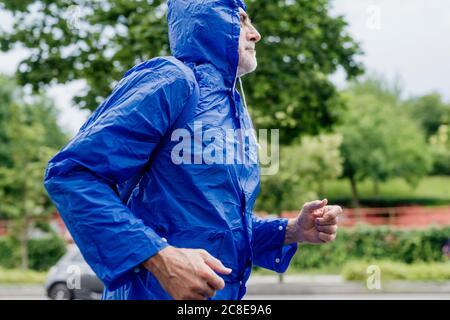 Uomo anziano che indossa un impermeabile blu che corre contro gli alberi nel parco