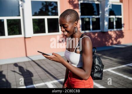 Giovane donna allegra con testina rasata che utilizza lo smartphone mentre camminando sul marciapiede in città Foto Stock