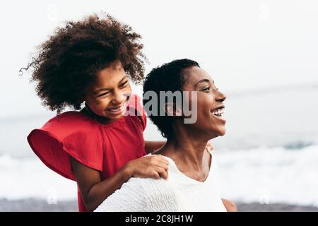 Madre nera e figlia che corrono sulla spiaggia al tramonto durante le vacanze estive - Famiglia persone che si divertono insieme all'aperto - Viaggi e happines