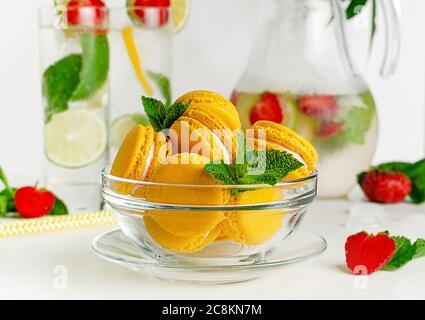 Macaroni gialli in un recipiente di vetro su sfondo bianco. Concetto di dessert francese Foto Stock