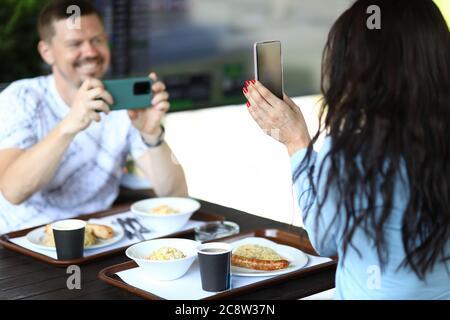 Donna sta tenendo smartphone nelle sue mani, l'uomo sta filmando la revisione della novità su smartphone in caffetteria.