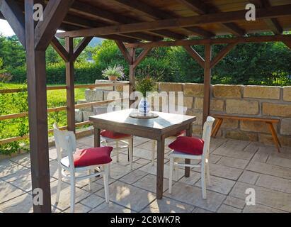 gazebo in legno tevere marrone - pergola con tavolo e sedie con cuscini rossi con parete in arenaria e pavimento con fiori estivi in giardino