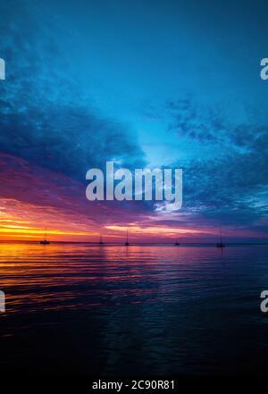 Mattina presto, alba sul mare. Cielo blu tramonto sul mare. Colori intensi. Alba paesaggio. Sole al tramonto. Foto Stock