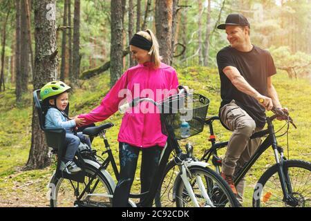giovane famiglia in bicicletta nella foresta con bambino in bicicletta seggiolino per bambini. sport attivi attività ricreative all'aperto Foto Stock