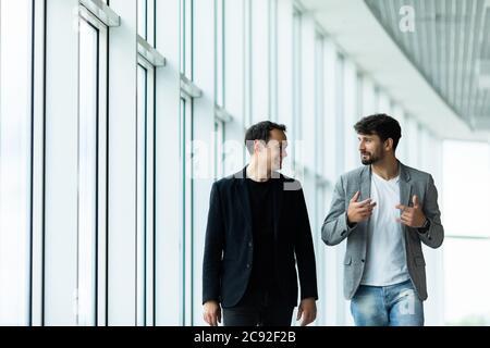 Ritratto di due partner d'affari concentrati vestiti in tuta formale a piedi e di conversazione Foto Stock
