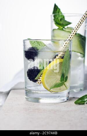 Bevanda rinfrescante estiva, tonica con foglie di limone, mora, cetriolo e basilico su sfondo chiaro.