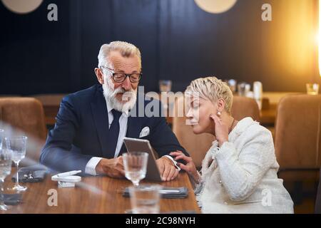 Bella coppia senior che guarda lo stesso tablet in ristorante, concetto pubblico, caucasiani maturi utilizzare la tecnologia moderna