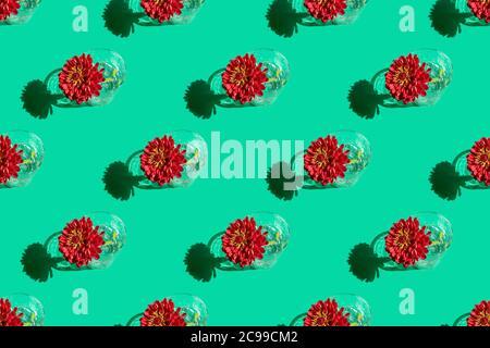 Motivo senza cuciture di un bicchiere con acqua e profondo fiore rosso Dahlia su sfondo verde. Concetto di fiori minimal in luce dura con ombre. Design d'arte.