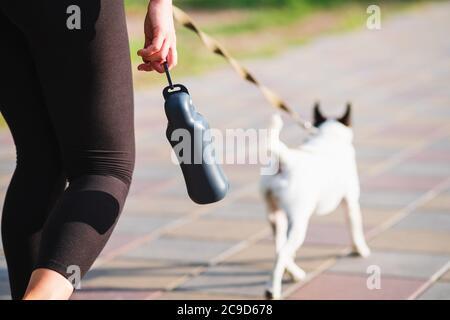 Stile di vita attivo con animali domestici in città, accessori, corsa con cani. Bere bottiglia in mano di donna, cane che cammina in background