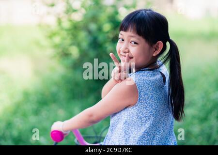 Ragazza asiatica che cavalca la sua bicicletta fuori con sorriso e felice Foto Stock
