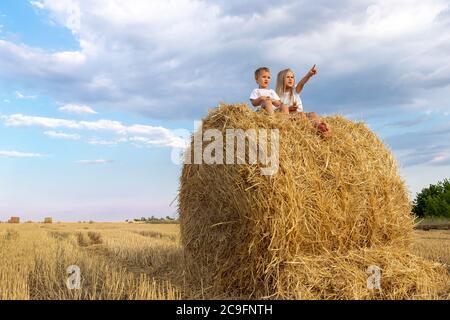 Due adorabili fratelli caucasici adorano divertirsi seduti sopra la balla di fieno d'oro sul campo di grano raccolto vicino alla fattoria. Felice infanzia e.