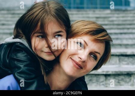 Giro in piggyback con mamma. Madre e figlia si abbracciano e sorridono.