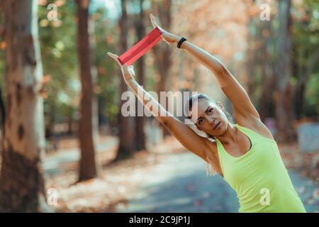 Donna che si esercita con la banda di resistenza all'aperto. Foto Stock
