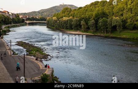 Torino, Piemonte, Italia. Luglio 2020. Splendida vista serale sul fiume po. La gente si rilassa lungo il fiume e il panorama della collina torinese.