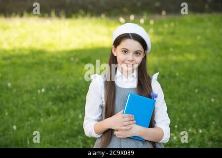 Elegante bambina scolastica con libro nel parco, sofisticato concetto scolastica. Foto Stock