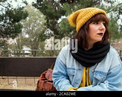 Giovane donna con cappuccio giallo di lana seduta su una panca preoccupato aspetto pensieroso. Concetto urbano autunnale. Foto Stock