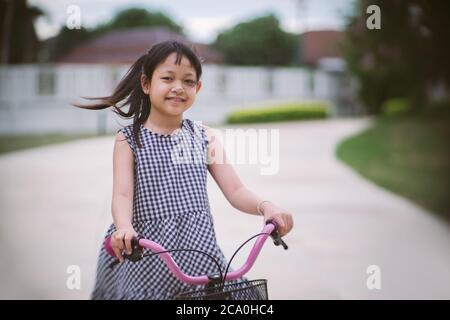 Ragazza asiatica che cavalca la sua bicicletta fuori con sorriso e stile happy.vintage Foto Stock