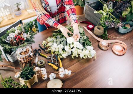 Proprietario di piccola impresa e bella donna fiorista che prepara un bouquet di fiori bianchi, godere di lavorare con piante e fiori. Botanica, concetto di piante Foto Stock
