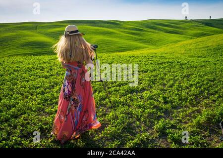 Val d'Orcia, Siena, Toscana, Italia, Europa. Donna bionda con cappello scatta foto in campi verdi.