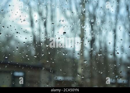 Pioggia sul vetro della finestra in una giornata cupa. Sullo sfondo, sagome offuscate di alberi e case. Autunno.