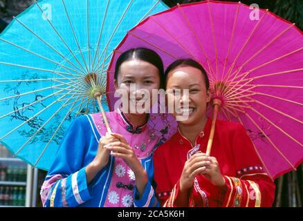 Due sorridenti giovane donna che indossa abiti tradizionali cinesi, tenendo un ombrellone in un parco, Yunnan, Cina Foto Stock