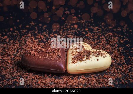 Due cioccolatini a forma di cuore fatti di latte e cioccolato bianco sulla tavola di ardesia, ricoperti di cioccolato grattugiato. Dessert per San Valentino.