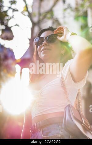 donna con occhiali da sole sorride mentre cammina per la città