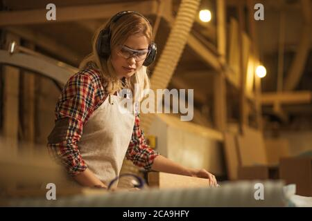 concentrato serio sicuro donna carpentiere si occupa di pezzo di legno, lei ascolta la musica, proteggere le sue orecchie dai rumori rumorosi in fabbrica Foto Stock