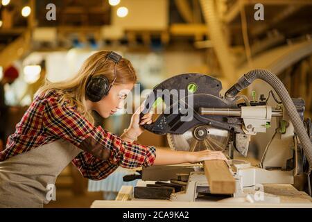 il carpentiere caucasico guida una sega circolare, lavoro concentrato della donna in fabbrica contrario a opinione che questo è un lavoro dell'uomo. il concetto di femminismo Foto Stock