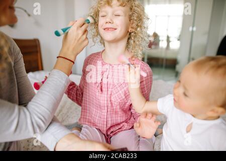 madre solletico sua figlia con un pennello in camera da letto. close up photo.funny bambina bionda con gli occhi chiusi è beiing messo sul trucco per il perf