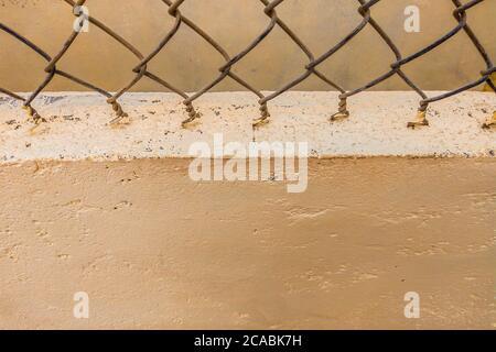 Primo piano vecchio recinto filo di ferro rete vintage sullo sfondo di cemento beige dipinto muro. Spazio di copia ideale per l'uso nel disegno o sfondo Foto Stock