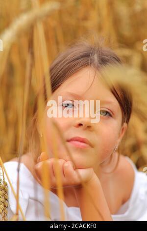 Bambina con un bouquet di fiori selvatici nelle mani in un campo di grano. Foto Stock