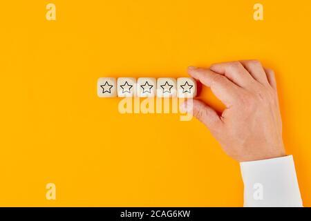 Mano di un uomo d'affari che mette cinque icona di valutazione stella su cubi di legno in una fila. Concetto di qualità del servizio e valutazione. Foto Stock
