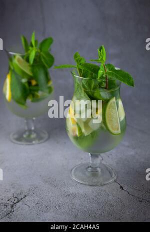 Mojito estivo con menta e calce rinfrescante cocktail con rum e ghiaccio in vetro su sfondo grigio. Cocktail mojito su tavolo in pietra. Vetro glassy alto per bevande