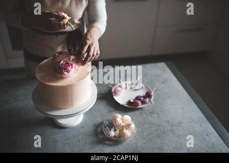 Donna che fa la torta decorando con rose di fiore che rimangono sul tavolo da cucina da vicino a casa. Giorno del matrimonio. Messa a fuoco selettiva. Foto Stock
