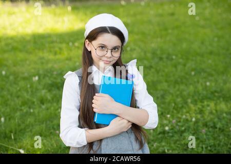 Elegante studentessa bambina studia con libro nel parco, imparando concetto. Foto Stock